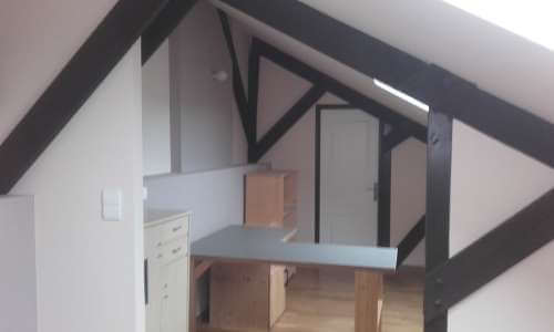 Rénovation mansarde avec poutres apparentes, vue de l'intérieur