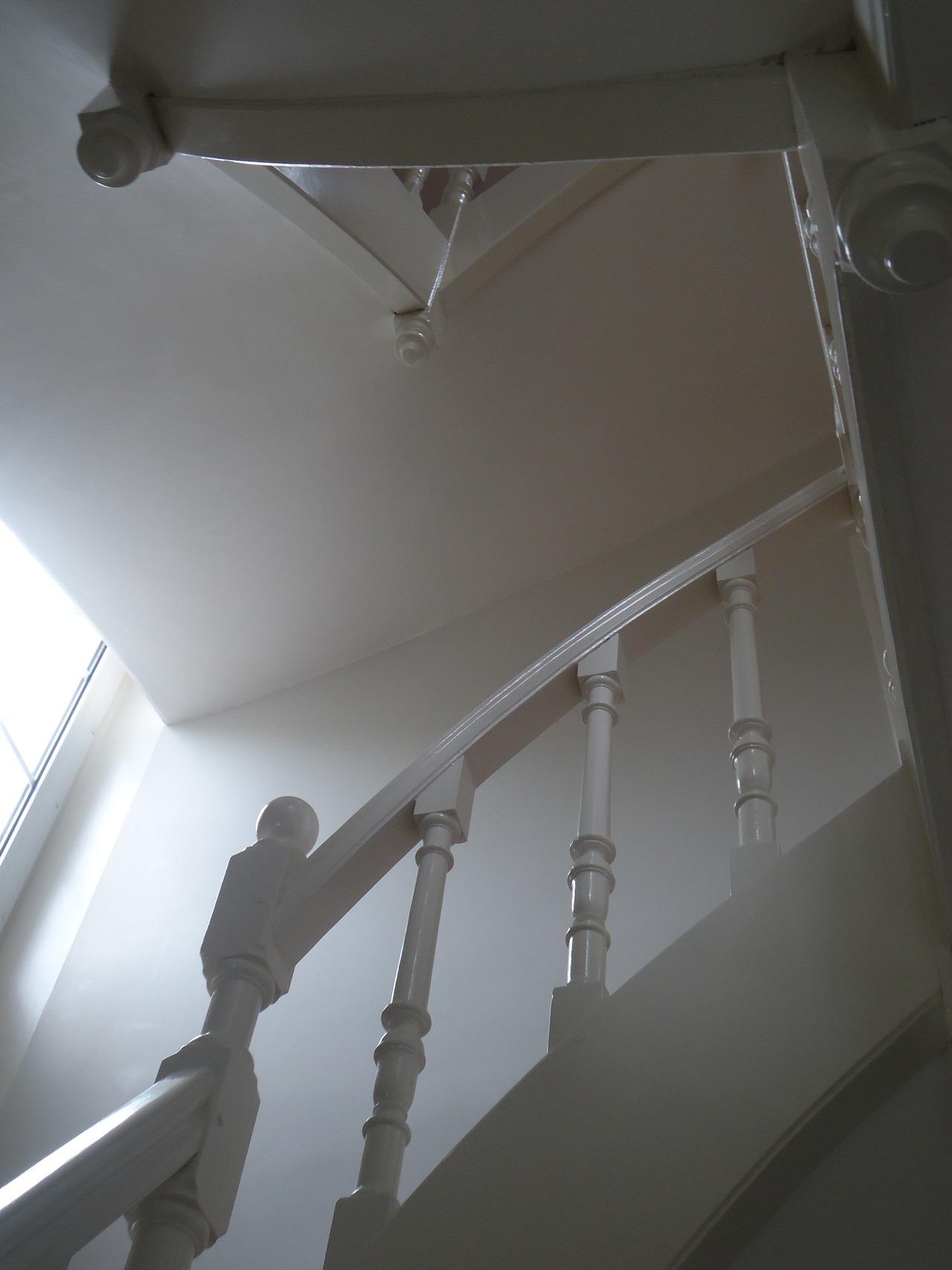 Vue du dessous, application de laque dans une cage d'escalier